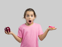 Donut or Apple. Little girl smiling and choosing between a apple and a donut Stock Photography