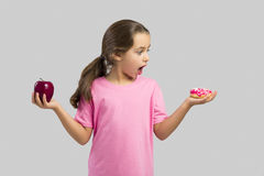 Donut or Apple. Little girl smiling and choosing between a apple and a donut Royalty Free Stock Images