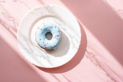 Donut bedeckt mit blauer Glasur und mit kleinen rosa Herzen auf einer weißen Platte auf einem rosa Hintergrund unter natürlichem  Stockfotos