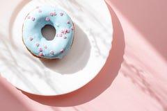 Donut bedeckt mit blauer Glasur und mit kleinen rosa Herzen auf einer weißen Platte auf einem rosa Hintergrund unter natürlichem  Stockfotografie