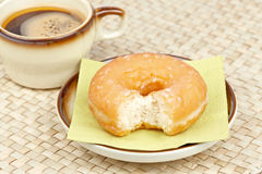 Donut bitten and coffee Stock Image