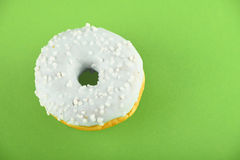 Donut with blue glaze sprinkles on green paper Stock Photo