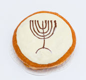 Donut with brown and white chocolate With a drawing of a menorah. Hanukkah holiday Stock Image