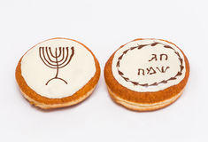 Donut with brown and white chocolate With a drawing of a menorah . Text - happy holiday. Donut with brown and white chocolate With a drawing of a menorah Royalty Free Stock Photo