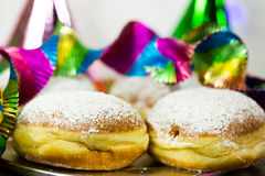 Donut for carnival, New Year`s Eve, colorful hats, streamers Royalty Free Stock Photos