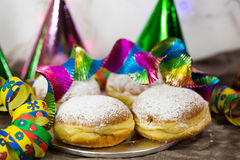 Donut for carnival, New Year`s Eve, colorful hats, streamers Stock Photos