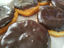 Delicious donut style pastry coated with chocolate and filled with cream. Donut with chocolat Stock Image
