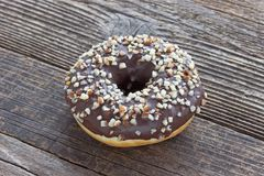 Donut with chocolate and chopped almonds on wooden table Stock Photography