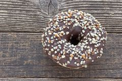 Donut with chocolate and chopped almonds on wooden table Stock Images