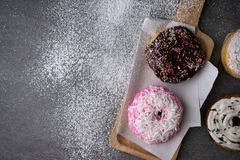 Donut with chocolate glazed and strawberry glazed in wooden tray on concrete table.  stock photo