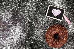 Donut with chocolate and heart drawing. Copy space royalty free stock photography