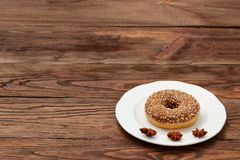 Donut with chocolate icing and nuts. Tempting aroma and taste of sweetness Royalty Free Stock Photography