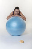 Donut choice. Attractive woman looking over a exercise gym ball at a single donut unsure what to do the temptation is just to much Stock Photography