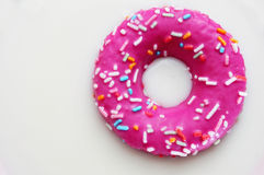 Donut coated with a pink frosting and sprinkles of different col Royalty Free Stock Photo