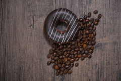 Donut and coffee beans. Donut with coffee bean on the wooden table Royalty Free Stock Photos