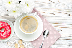 Donut and coffee, flowers on wooden background Royalty Free Stock Photos