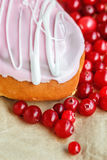 Donut covered with pink icing and cranberry on a crumpled wrapping paper background. Top view. Glazed bun with colored glaze Royalty Free Stock Photo