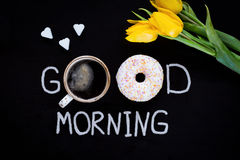 Donut, cup of coffee, heart shaped sugar cubes and yellow tulips on black background Royalty Free Stock Image