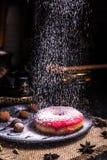 Donut in der Zuckerglasur mit N?ssen in einer Schokoladentr?ffel in einem Restaurant Pulverisierte Zuckerglasur stockbild