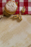 Donut and dreidles - Jewish Hanukkah Symbols on rustic red check Royalty Free Stock Images
