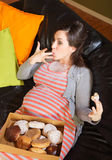 Donut Eating Pregnant Woman on Sofa. Pregnant woman with box of donuts licking her fingers royalty free stock photo