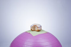 Donut on fitness ball. Bad workout concept royalty free stock photos