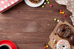 Donut, gift box and coffee. Donuts, gift box and coffee on wooden table. Top view with copy space Royalty Free Stock Photos