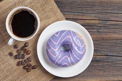 Donut with glaze and coffee. Donut with violet glaze and cup of coffee on old wooden table, top view stock photo
