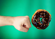 Donut got kicked. With hand isolated on green background Royalty Free Stock Images