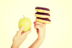 Donut or green apple - hard choice. Stock Image