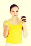 Donut or green apple - hard chose. Stock Images