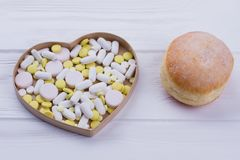 Donut and heart-shaped box with pills. stock images