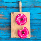 Donut with heart sprinkles on blue colorful wooden background. D Royalty Free Stock Image