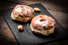 Donut with icing and rose jam. Royalty Free Stock Images