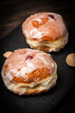 Donut with icing and rose jam. Royalty Free Stock Image