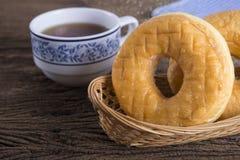 Donut im Bambuskorb mit einer Tasse Tee auf Holztisch Stockfoto