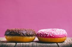 Donut mit besprüht auf einem Holztisch und einem rosa Hintergrund Zwei Arten Schaumgummiringe Kuchen und Bonbon Lebensmitteldetai Lizenzfreie Stockbilder