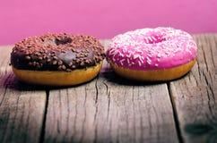 Donut mit besprüht auf einem Holztisch und einem rosa Hintergrund Zwei Arten Schaumgummiringe Kuchen und Bonbon Lebensmitteldetai Stockbilder