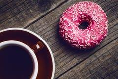 Donut mit besprüht auf einem Holztisch und einem rosa Hintergrund Zwei Arten Schaumgummiringe Kuchen und Bonbon Lebensmitteldetai Lizenzfreies Stockfoto
