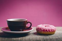 Donut mit besprüht auf einem Holztisch und einem rosa Hintergrund Zwei Arten Schaumgummiringe Kuchen und Bonbon Lebensmitteldetai Stockfotografie
