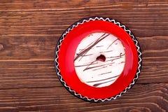 Donut mit Schokolade auf einer roten Untertasse Lizenzfreies Stockbild