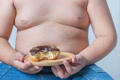 Donut in obese fat boy. Donut in hand obese fat boy, junk food can cause obesity Royalty Free Stock Images