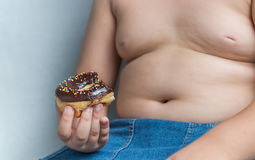 Donut in obese fat boy. Junk food can cause obesity Royalty Free Stock Photos