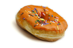 Donut with Orange Frosting and Rainbow Sprinkles. A donut with orange frosting and rainbow sprinkles against a white background Stock Image