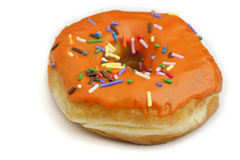 Donut with Orange Frosting and Rainbow Sprinkles. A orange frosted donut with rainbow sprinkles Stock Image