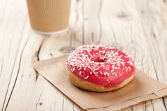 Donut and paper cup on wooden table Stock Photography