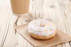 Donut and paper cup on wooden table Stock Images