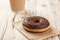 Donut and paper cup on wooden table Royalty Free Stock Image