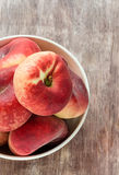 Donut peaches in bowl over wooden background Stock Images