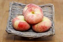 Donut peaches, saturn peaches in wicker basket Stock Photos